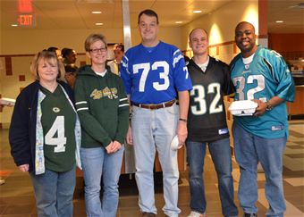 "Brig. Gen. (Dr.) Kory Cornum, Keesler Medical Center commander, center, stands with several medical center ""Dragon Medics"" in the facility's Hungry Dragon dining facility Jan. 24, during ""Jersey Day"" at Keesler Air Force Base. He is sporting the jersey he wore as a U.S. Air Force Academy Falcons defensive end 34 years ago. Cornum has been selected to become the Air Mobility Command command surgeon after serving in his current post for four year. Showing their colors are, from left, Susan Givens,2st Lt. Cristi Dueker-Bray and Senior Airman Daniel Worsham, 81st Medical Operations Squadron, and Master Sgt. Gene McCants, 81st Medical Group."