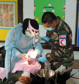 Malaysian Armed Forces dentists work on the teeth of a local Thai villager during a cooperative health engagement Feb. 13 at the Ban Sa la Kai Fub School as part of Exercise Cobra Gold 2014 in Sukhothai province, Kingdom of Thailand. Along with the CHE, four schools are being constructed throughout Thailand and a medical symposium will be held as part of the humanitarian and civic assistance projects taking place during the annual exercise. CG 14, in its 33rd iteration, demonstrates the U.S. and the Kingdom of Thailand's commitment to their long-standing alliance and regional partnership, prosperity and security in the Asia-Pacific region. (U.S. Army photo by Spc. Tyler Meister/Released)