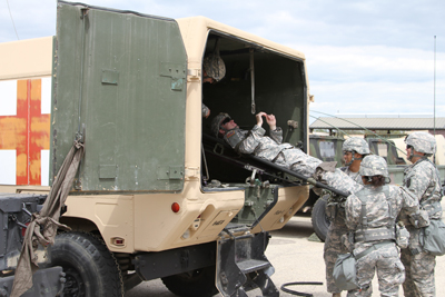 Soldiers with the 4th Maneuver Enhancement Brigade, 1st Infantry Division, practice their medical skills for an upcoming Expert Field Medical Badge competition by unloading a mock casualty from a Field Line Ambulance at Fort Leonard Wood, Mo., on May 2, 2014. The 4th MEB is scheduled to take a group of 12 Soldiers to the upcoming 1st Infantry Division EFMB competition at Fort Riley, Kan.