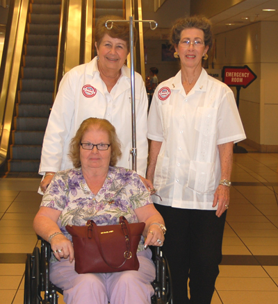 Keesler Medical Center volunteer patient escorts Penny Hershberger, left, and Victoria Todd assist Charlotte Taylor May 27 as they begin working in the formerly all-male service that began in 1980. (U.S. Air Force photo by Steve Pivnick)