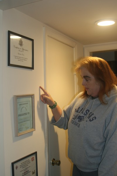 Joyce Ammen, founder and total staff of Operation Care, a nonprofit that provides food and non-perishable items to servicemen and military families, stands in her Lorton, Va., townhouse with framed thank-you letters from units she's worked with.
