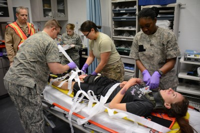 A team of medical professionals care for a victim of a mock car accident in the Blatchford-Preston Complex Clinic during an exercise at Al Udeid Air Base, Qatar, Dec. 15. The exercise consisted of a car accident with eight victims. All patients were transported to the clinic where they received emergency medical treatment. More than 50 first responders participated in the exercise. (U.S. Air Force photo by Tech. Sgt. James Hodgman/Released)