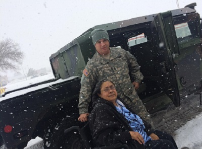 Sgt. 1st Class Christopher Vaillancourt, Headquarters and Headquarters Company, 717th Brigade Support Battalion, takes a chilly photo with a Roswell citizen he helped transport to the Fresenius Medical Care center Dec. 29. One of the missions currently being performed by members of the New Mexico National Guard is the transportation of Roswell, N.M., citizens in need of dialysis treatments. Citizens were snowed in to their homes due to a winter blizzard that caused roads to be impassable. For at least two days, local members of the National Guard traversed the icy, snowpacked conditions to help citizens in need. (Courtesy photo)