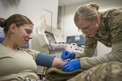 Spc. Lauren O'Neal, 153rd Blood Support Detachment medical laboratory technician, prepares Spc. Samantha Criscio, Guard Force, to give platelets at Craig Joint Theater Hospital on Bagram Air Field, Afghanistan, Dec. 31, 2015. In order to extract platelets, a critical life-saving blood component, apheresis machines are used to draw blood and return the unused portions to the donor. (U.S. Air Force photo/Tech. Sgt. Robert Cloys)