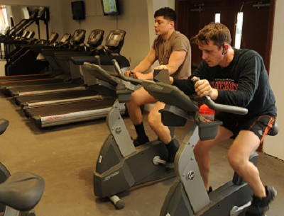 "160104-N-SD965-007 ROTA, Spain (Jan. 4, 2016) Builder Constructionman Sean Rodriguez-Lopez, left, and Electronics Technician 3rd Class Tony Juarez, assigned to Naval Mobile Construction Battalion (NMCB) 1, ride stationary bikes during the NMCB 1 ""Heroes to Home Bike and Run Challenge"" at Camp Mitchell on Naval Station Rota, Spain, Jan. 4, 2016. ""Heroes to Home"" is a fitness challenge to accumulate the 12,378 miles, the total distance from the two deployment sites of Rota, Spain and Guam back to Gulfport, Miss. (U.S. Navy photo by Mass Communication Specialist 1st Class Brannon Deugan/Released)"